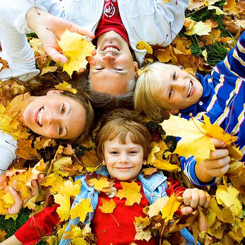 Foto Familie liegt mit 2 Kindern im Laub